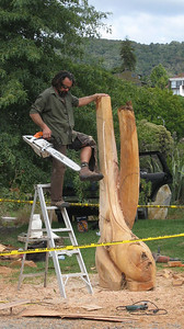 Will Ngakura has just finished cutting the tops off of his sculpture with a chain saw.