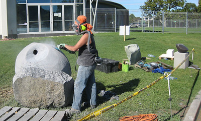 Sculptor, Jocelyn Pratt, has shaped the stone and is now smoothing it.