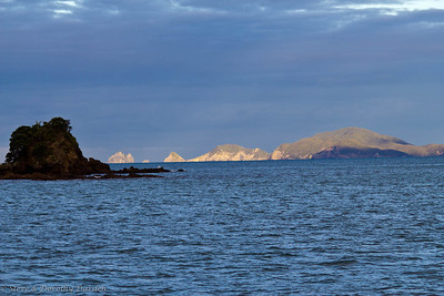 Cape Brett lighted at sunset as seen from Te Pahi Islands