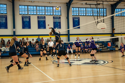 Varsity volleyball member Carolyn Bruce attacks the net during a home game