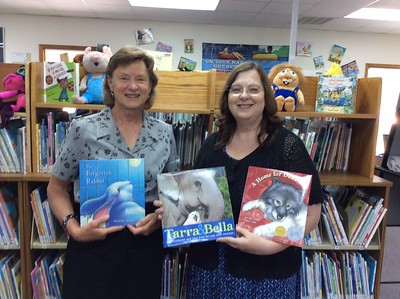 Anne Grindle, MARC Education Director, presents children's books promoting the humane treatment of animals to Karen Tittle, librarian at the May Justus Memorial Library