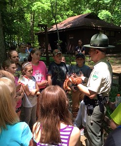 Students  from North Elementary look on as Ranger Murray shows them a corn snake. PhotobyKellyBaggett.