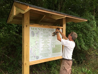 Friend of Mountain Goat Trail Alliance John Owsley is shown putting finishing touches on one of two new sign kiosks
