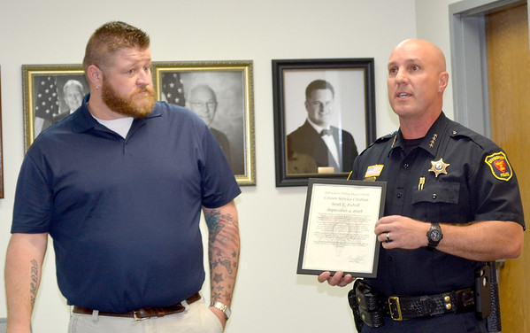 Scott E. Ruholl listens as Effingham Police Chief Jeff Fuesting describes how he helped police during an icident in the city recently. Ruholl was given a Citizen Service Citation for his efforts. Dawn Schabbing photo