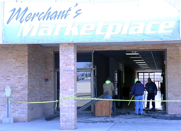 Employees of Dan's Glass Unlimited and a staff member from the Village Square Mall work to repair damage after a vehicle drove into the mall then through the mall in late January. File Photo