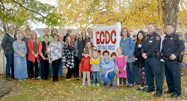Presbyterian Women members, ECDC staff and board members, community members, children from the ECDC and Effingham police officers are pictured in from of the Effingham Child Development Center sign Monday afternoon. Kaitlin Cordes photo