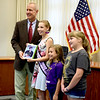 Gov. Bruce Rauner stands with area childhood cancer survivors including Mitchell Coffin on the iPad image, Elizabeth Weidner, Grace Brummer, and Kinley Briggs. On Monday he proclaimed September 2018 as Childhood Cancer Awareness Month. Dawn Schabbing photo