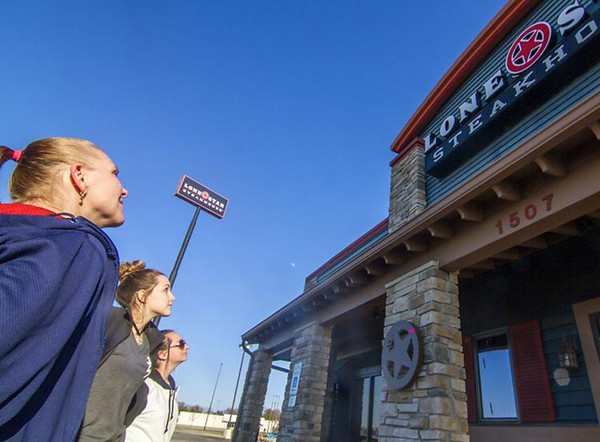 Former Lone Star Steakhouse and Saloon employees, from left, Jennifer Evans, Hailey Olsen and Gena Gagliano look up at the restaurant after giving their final goodbyes in February. File Photo