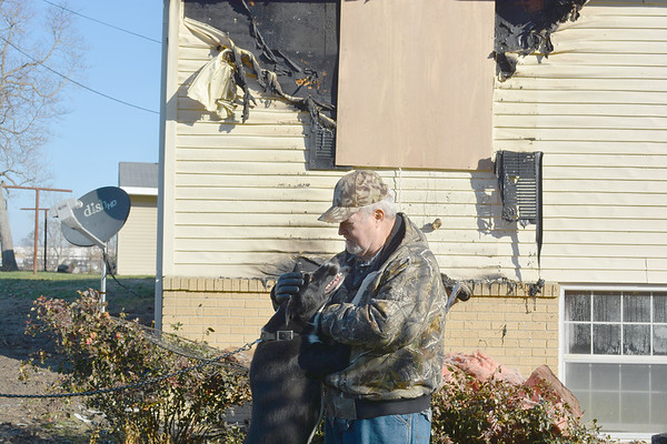 Kenny Tucker with his dog Buddy in front of his house the day after the house fire. Buddy alerted Tucker to the fire which allowed him to escape the flames.