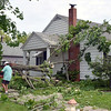 Neighbors clean up a fallen tree in the front yard of Lucille Schroeder's house Sunday afternoon in Altamont. Kaitlin Cordes photo