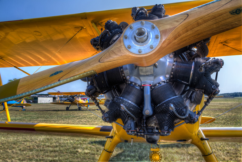 Two bright yellow Steerman biplanes sit at the Jennings, LA fly-in on a sunny fall day. Photo by Tim Stanley Photography.