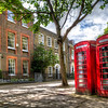 A Pair of Red Phone Booths<br /> Walking around in London, you actually do see the iconic red phone booths from time to time. But I'm not sure that anyone but tourists actually use them, as most people have cellphones now. I did see one that had an ATM inside. I thought that was a clever use for the booth. In our travels, we also saw a field of old phone booths; a red 'junk yard' of sorts.  This pair was by some apartments of a busy square. It was hard to take a shot without the tourists playing around them all the time. Nothing like a pesky tourist getting in the way of another tourist's photo.