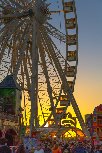 Ferris Wheel Sunset<br /> Sunset at the carnival is a fun time. There is a transition that takes place between the colors and sites of the day to the neon and mystique of the night.