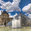 The Louvre Pyramid and Fountains<br /> The Louvre Palace in Paris is well known for many things, such as how large it is, the quality of the art inside and the large, glass pyramid outside. The Louvre Pyramid is made of glass and metal, that breaks down to a total of  673 glass panes. It is surrounded by three smaller pyramids and several fountains in the main courtyard.