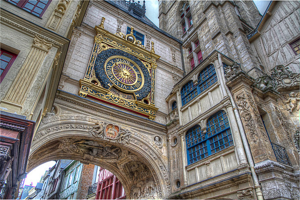 "The Great Clock<br /> With the invention of clocks in the Medieval Ages, many cities hung clocks in public areas. Le Gros Horloge or ""The Great Clock"" in Rouen, France was built in the fourteenth century on the archway over a gate in the ancient Roman walls and rang the bells of the nearby Gothic belfry. The city installed a face on the clock in 1409, with just one hour hand to tell the time and a globe showing the phases of the moon. It was later rebuilt in 1527-1529.  On the underside of the arch are depictions of sheep showing the importance of the wool trade in Rouen and the Paschal Lamb, which has been part of Rouen's coat of arms since the 14th century."
