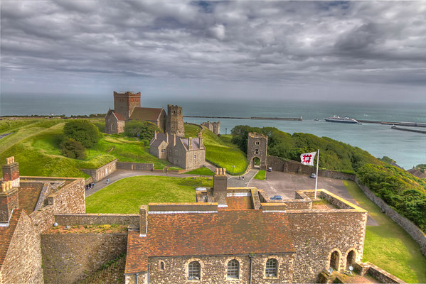 View from the Great Tower<br /> Spectacularly situated above the White Cliffs of Dover, this magnificent castle has guarded England's shores from invasion for 20 centuries. From High atop the Great Tower, you can see over the grounds of Dover Castle, including the church and lighthouse on the far hill. In the distance is a ferryboat leaving the harbor, carrying passengers, cars and trucks across the English Channel towards France.