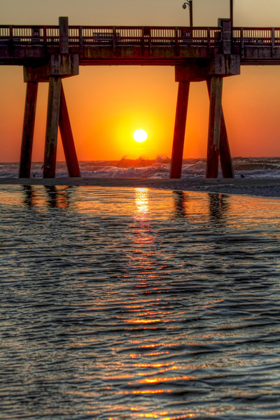 """A Captive Sunrise<br /> Sometimes a different viewpoint of the same subject can be just as interesting, but in a different way. This sunrise, framed by the Pensacola Beach Fishing Pier, was shot moments before """"Sunset Under the Pier"""", but with a much stronger lens. Which is better? You decide. I like them both, for different reasons. <br /> Those that follow my blog know that I'm fond of the wider angle shots, but I'm trying to learn to see the closer viewpoint too. The problem now is I want to carry two cameras with different lenses all the time."""