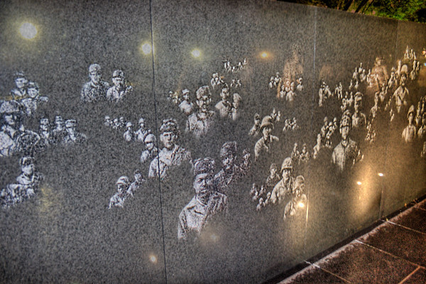 Soldiers in the Wall<br /> The south side of the triangular shaped memorial is a 164-foot-long black granite wall with photographic images sandblasted into it depicting soldiers, equipment and people involved in the war. At night, the eerie feeling of those faces from the past is very moving.
