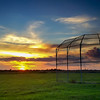 Ball Field Sunset<br /> So I'm driving home from an after-work meeting and notice that there might be a pretty sunset. We don't get a lot of these during the summer, so I thought I might try to catch this one. The light was fading fast and the only place to pull over was behind a middle school in their faculty parking lot. Their trash dumpsters just wouldn't work for a good foreground, so I hurried to the other corner by the ball fiield backstop. Of course, I didn't have my DSLR, but I did have the iPhone. Beggars can't be choosey.