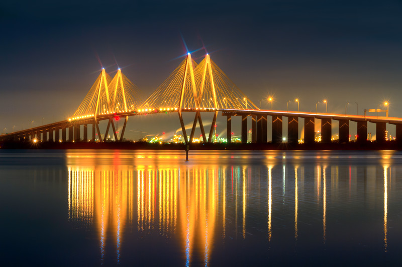 Spanning the Houston Ship channel between Baytown and La Porte on Highway 146, the Fred Hartman Bridge casts beautiful reflections at night. Photo by Tim Stanley Photography.
