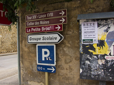 Signs pointing to a fourteenth century tower, an eighteenth century Lavoir, the monks' cellars, and a roadside park, in the village of Beze.