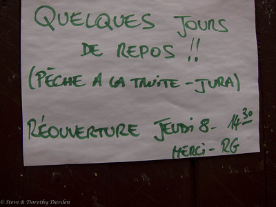 Sign on a shop that says:  Several days of rest!! (Trout fishing at Jura) Reopening on Thursday at 1430 hours.  Thank you - RG