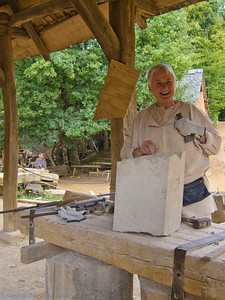 A volunteer from the UK proudly displays the flat surface she has handcrafted on this large stone.