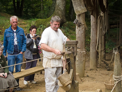 Rope maker demonstrates his machine for twisting four cords together into a rope.