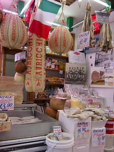 Enormous cheeses, herring and wet salted cod fish surround a  photo of favorite local rugby team.