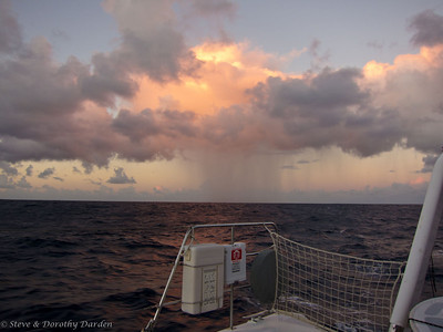 Isolated shower astern at sunrise on the fifth day out.