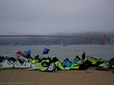 Board surfers waited on the beach while ETNZ Americas Cup boat sailed past the Golden Gate Bridge.