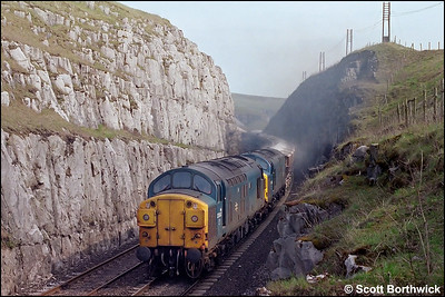 37047+37100 blast away from Peak Forest through Dove Holes cutting whilst working 6J46 Peak Forest South SS-Hope Street (Salford) on 22/04/1987.