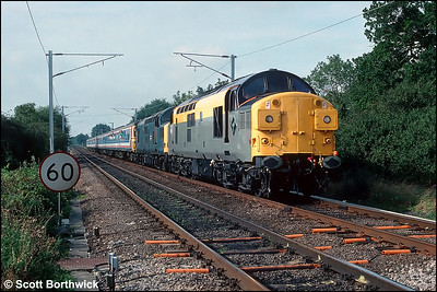 37023+37245 hauling 2 x Class 312 EMU's approach Ely North Jnct forming 2G32 0930 Cambridge-Kings Lynn on 14/09/1991. The train was an additional working in connection with the Network South East 'Network Gala Day 1991'. Note the recently installed masts for the Kings Lynn line electrification scheme yet to receive their overhead wires.
