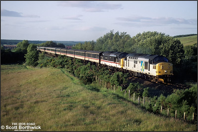 The late evening sun highlights the arches of the distant Culloden Viaduct as 37214 & 37510 shatter the peace at Castletown with 1M16 2020 Su-F Inverness-London Euston at 2054 on Monday 12 July 1993.