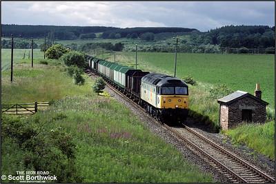 47314 'Transmark' passes Woodside, Elgin whilst working 6H51 1435 MThO Inverness-Elgin timber etys on 12/07/1993.