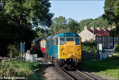 31128 'Charybdis' slows to exchange the token at Newbridge LC whilst working 1T10 0900 Pickering-Grosmont on 15/09/2012. The train should have run to Whitby, however, a gas leak at Ruswarp had closed the Esk Valley line, so the service terminated at Grosmont.