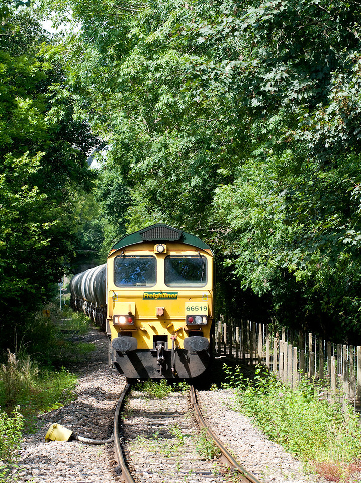 100811  As we drove through Moorswater we saw the train was under the bridge at Coombe station. A quick drive and a shot was obtained of it approaching the junction (it was not hanging around either1) 66519 on 6C66  14:43 Moorswater-Westbury approach Coombe ground frame