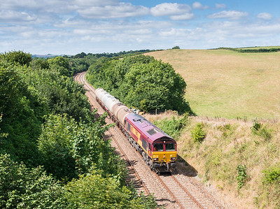 090813  With it being a very 50-50 time for the sun we were well pleased when this came in a big blue patch.66075 passes Shillingham,near Forder with an early running 6C39  FO 11:50 St.Blazey-Newport ADJ...The assistant mans the tripod with the camera from the dark side.