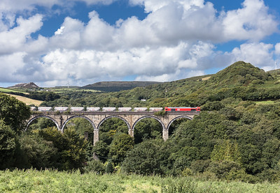 150817  After a 3 hour break at Burngullow 66206 gets on the move again and crosses Gover viaduct.Again the landscape is peppered with remnants of the China clay industry with spoil heaps dominating the background.The one top left marks the edge of the Blackpool china clay works.