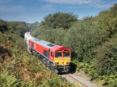 220817  1446....With the spoil heap visible above Nanpean in the background,66206 passes Foxhole with 13 loaded CDA's forming the second portion of 6P24 15:25 Parkandillack-Fowey..the assistant mans the tripod.