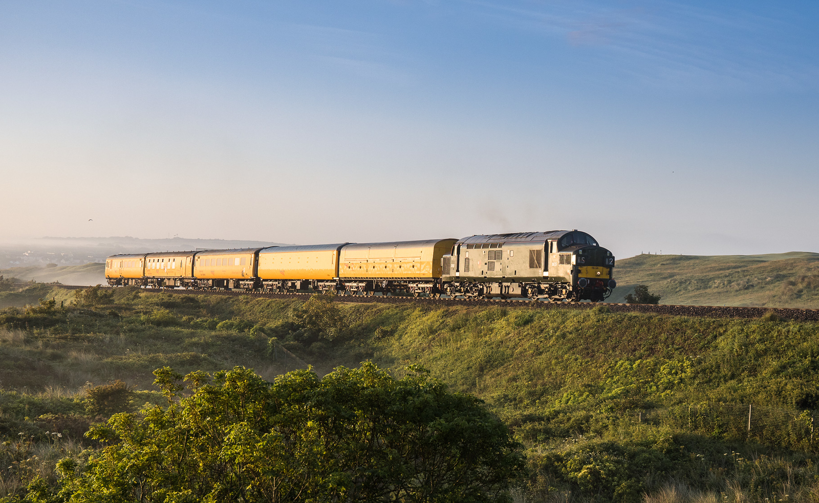 140617. With West Cornwall golf club in the back ground 37057 heads past the sand dunes of the SW coastal path and takes  3Q52 2229 Exeter Riverside N.Y. to Penzance towards St Ives.