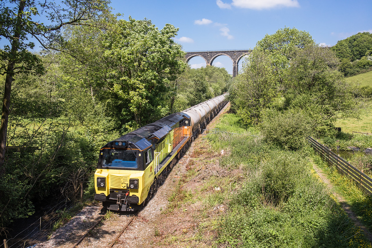 250517  . 70812 heads the late running 6C36  ThO  1138 Moorswater-Aberthaw cement works under the roadbridge at Coombe