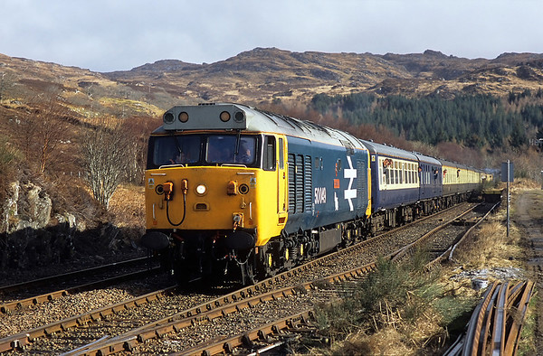 As the sun begins to break through the clouds 50049 nears Arisaig station on 1Z23 10:20 Fort William-Mallaig 05/03/05