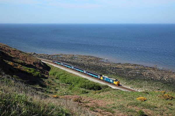 37402 runs along the rocky shore past Lowca at the rear of 2C40 08:42 Carlisle -  Barrow in Furness, 03/05/17