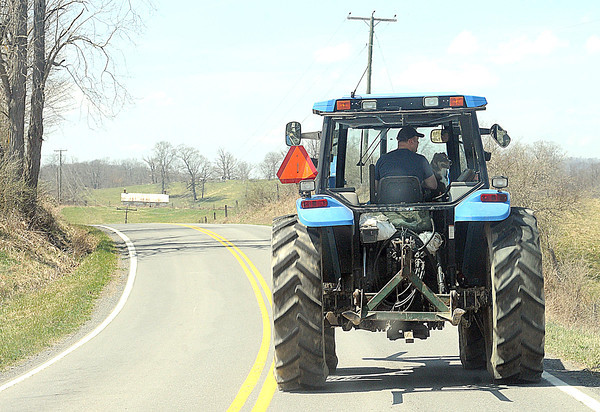Man with his best friend riding his tractor on route 3 in Monroe County.<br /> Rick Barbero/The Register-Herald