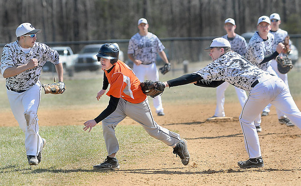F. BRIAN FERGUSON/THE REGISTER-HERALD=Westside's Dakota Paynter, left, watches as Richwood's Caleb Louden, center, is tagged out by pitcher Drew Bragg, right, during a run-down play in Fayetteville on Wednesday morning.
