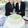 """Rev Bob Daniels, left, and Rainelle mayor, Andrea """"Andy"""" Pendleton, portraying, Mrs and Mrs John Raine, cut the cake for the Town of Rainelle Centennial Celebration.<br /> Rick Barbero/The Register-Herald"""