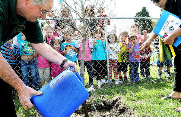 F. BRIAN FERGUSON/THE REGISTER-HERALD=Children at Lollipops and Lullabies Daycare watch as Allen Waldron with the West Virginia Division of Forestry; left, and Sherrie Hunter with Make it Shine, right, plant a tree in  front of their day care on Dry Hill Road as part of an Arbor Day celebration.