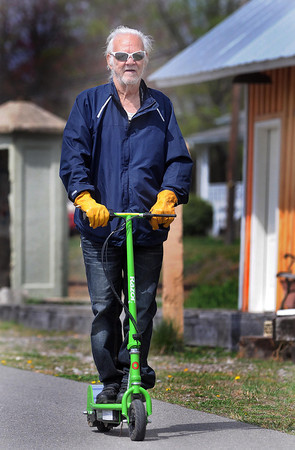 F. BRIAN FERGUSON/THE REGISTER-HERALD=Green Machine=Charles Dower of Oak Hill has little concern over the cost of gas as he drives his electric scooter along the White Oak Rail Trail on a a warm, spring Tuesday morning.