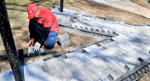 F. BRIAN FERGUSON/THE REGISTER-HERALD=Aspen employee Carlos Fuebtes measures some brick to be layed at the new Memerial for Upper Big Branch outside the Raleigh County Courthouse on Tuesday afternoon.